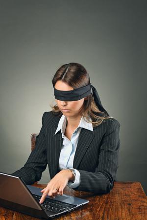 Mujer de negocios con los ojos vendados con la computadora portátil. La indecisión y la incertidumbre conceptual