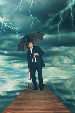 storm coming: Businessman with umbrella facing storm coming. Finance and job concept