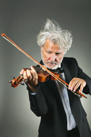 concerto: Senior violinist with shining and upset white hairs . Music and concerto concept