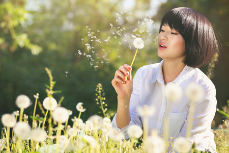 Beautiful asian girl blowing dandelion . Spring and outdoor relax