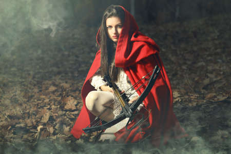 the little red riding hood: Hermosa caperucita roja esperando el lobo con ballesta en un bosque de niebla