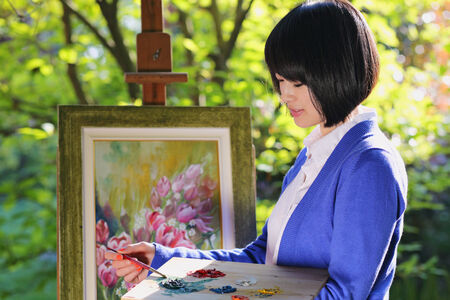 oudoor: Beautiful young woman painting a flower canvas oudoor  . Creativity and hobby Stock Photo