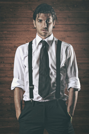 Fashion model  with black suspenders . Bold expression and wood texture Stock Photo