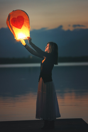prayer candles: Young woman with flying chinese sky lantern   Making a love wish