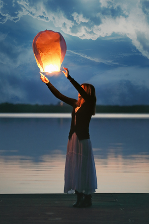 Chinese sky lantern flying away , carrying young woman wish photo