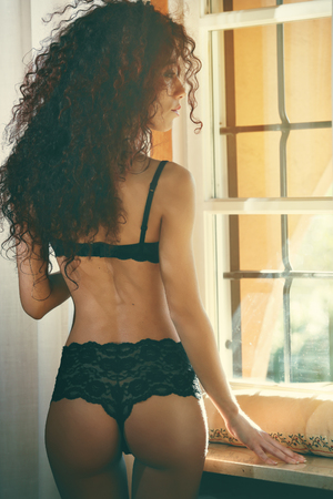 boudoir: Beautiful woman in black lingerie looks out of the window  Stock Photo