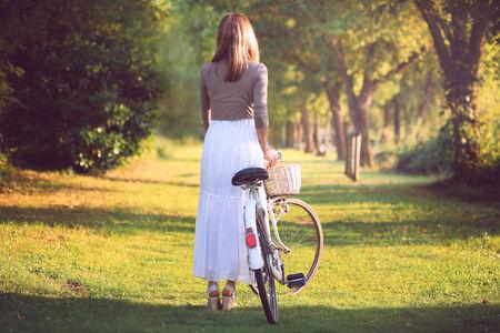 bicicleta retro: Mujer blanca vestida con una bicicleta de la vendimia en la luz del atardecer Foto de archivo