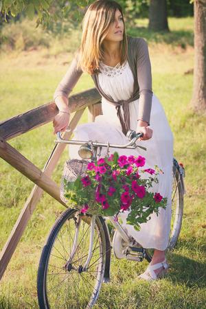 bicicleta retro: Joven y bella mujer en una bicicleta retro con flores. Retrato romántico
