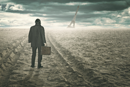 Businessman in a desert and surreal beach looks at destroyed Tour Eiffel . End of civilization