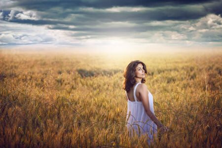 Beautiful woman in a corn field with dramatic sky . Sunset light photo