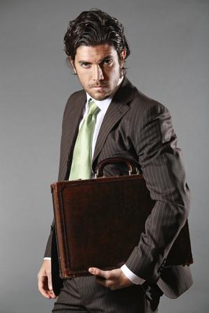 business model: Fashion business model poseren met aktetas. Grijze achtergrond Stockfoto