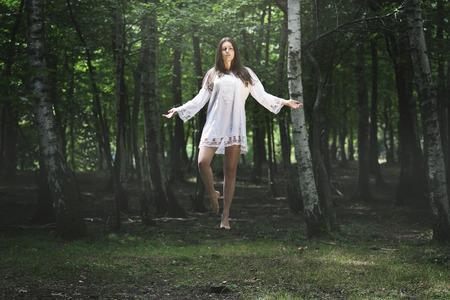 Mujer levitación hermosa en el bosque. Fantasía y surrealista