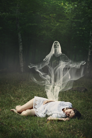 Soul of a sleeping woman leaving her body in a forest  . Surreal and halloween concept photo