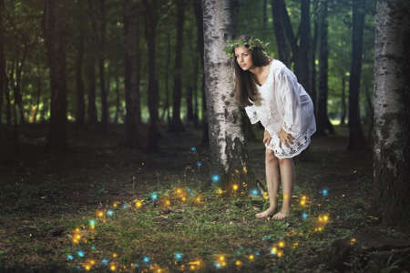 Beautiful girl staring at the dance of the forest spirits . Fantasy and fairy tale