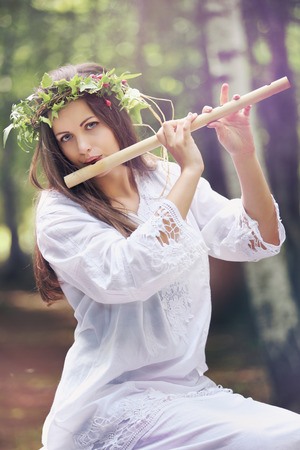 Beautiful forest nymph playing a flute. Romance and fantasy Standard-Bild