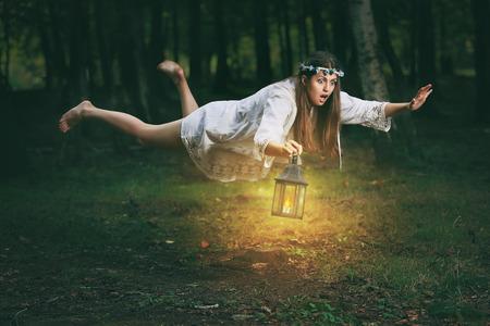 Jonge vrouw met geschokte uitdrukking vindt zichzelf vliegen in het bos. Fantasie en surrealistische Stockfoto