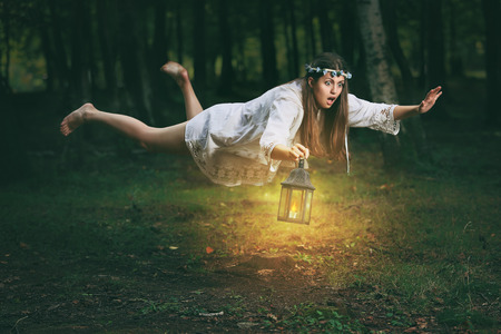 Young woman with shocked expression finds herself flying in the woods. Fantasy and surreal