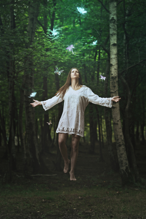 levitation: Beautiful woman flying among strange butterflies in a forest . Fantasy and surreal  Stock Photo