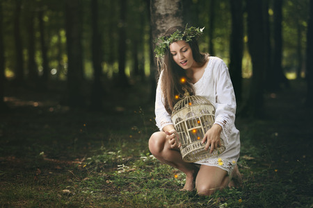 Beautiful girl frees forest fairies from a bird cage. Fantasy concept Stock Photo