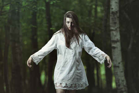 vampire girl: Dark girl with evil expression in the woods. Horror and halloween conceptual