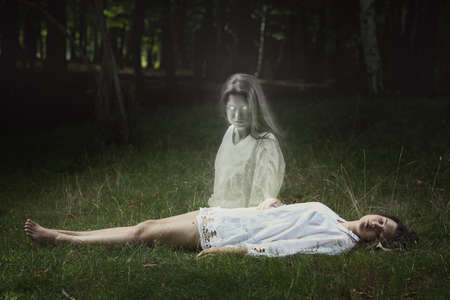 Scary ghost of a sleeping girl looks directly into the camera . Horror and Halloween concept Stock Photo