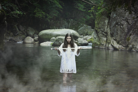 evil girl: Beautiful dark girl with a sword in a mountain stream. Fantasy and halloween concept