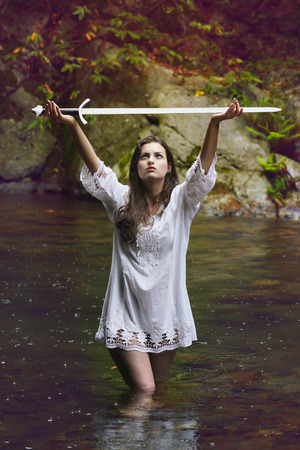 Beautiful woman lifting a sword to the sky . Fantasy and legend conceptual photo
