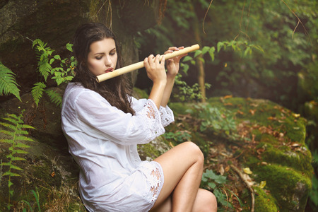 Beautiful woman playing  flute after the rain in a forest . Romance and fantasy