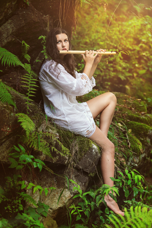 wood nymph: Beautiful dryad playing flute in a forest after the rain. Romance and fantasy