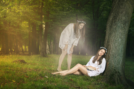 Beautiful girl in astral projection looks herself sleeping . Mystical and weird concept photo