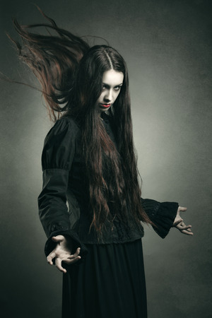 mage: Dark witch calling black powers . Halloween and horror studio shot