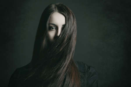 Dark portrait of a young woman with long hair . Halloween and horror concept