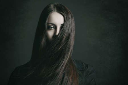 Donker portret van een jonge vrouw met lang haar. Halloween en horror-concept