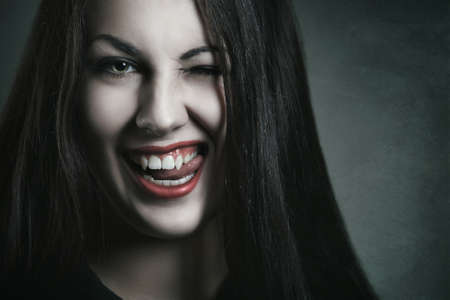 beautiful vampire: Evil and amused expression on beautiful vampire face . Halloween and horror Stock Photo