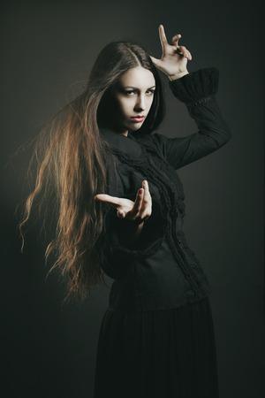 美しい暗い魔女、呪文します。ハロウィーンとファンタジーのスタジオ ショット