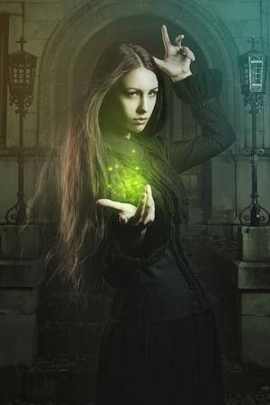 美しい若い魔女の呪文します。ハロウィーンとファンタジーのスタジオ撮影