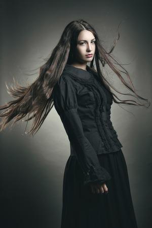 Beautiful dark girl with long flying hair . Halloween and dark studio shot Standard-Bild