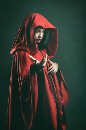 赤いマントを持つ美しい女性の肖像画を暗い。ファンタジー スタジオ ショット