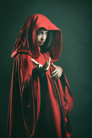spells: Dark portrait of a beautiful woman with red cloak . Fantasy studio shot Stock Photo