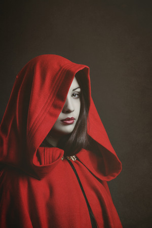 little red riding hood: Dark portrait of a red hooded woman . Fantasy studio shot Stock Photo