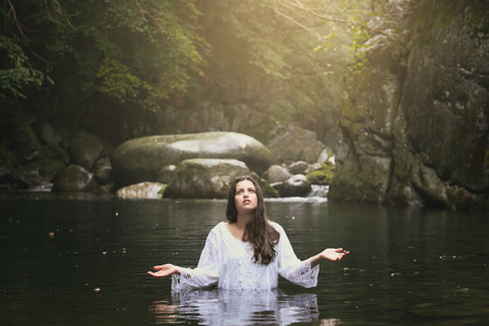 Beautiful young woman praying in a mountain stream . Fantasy and surreal photo