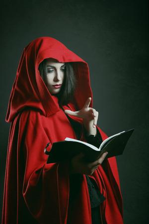 caperucita roja: Oscuro retrato de una mujer con capucha roja leyendo un libro. Fantas�a foto de estudio