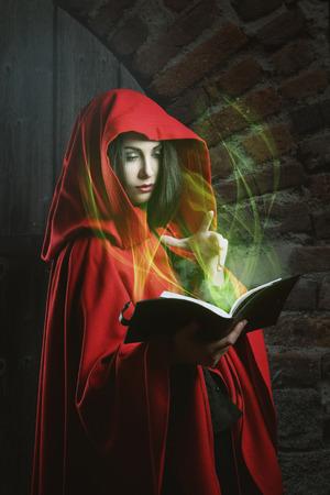 Rode kap vrouw lezend in een magische boek. Donkere fantasie portret