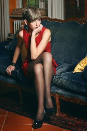 velvet dress: Beautiful short hair model seated on a velvet coach .Elegant red dress