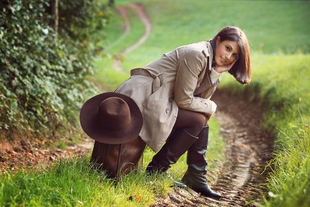 femme valise: Belle femme assise sur une valise en cuir vintage. Banque d'images
