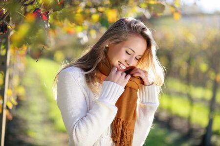 Smiling woman enjoying autumn sun in the countryside