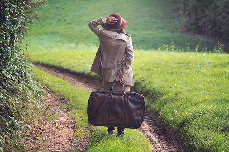 femme valise: Femme élégante perdu dans une route de campagne. Extérieure conceptuelle