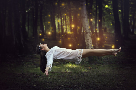 Woman levitation in the forest surrounded by fairies . Fantasy and surreal