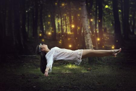 Vrouw levitatie in het bos omgeven door feeën. Fantasie en surrealistische