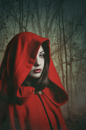 sorceress: Dark red hooded woman in a misty forest . Fantasy and surreal shot Stock Photo